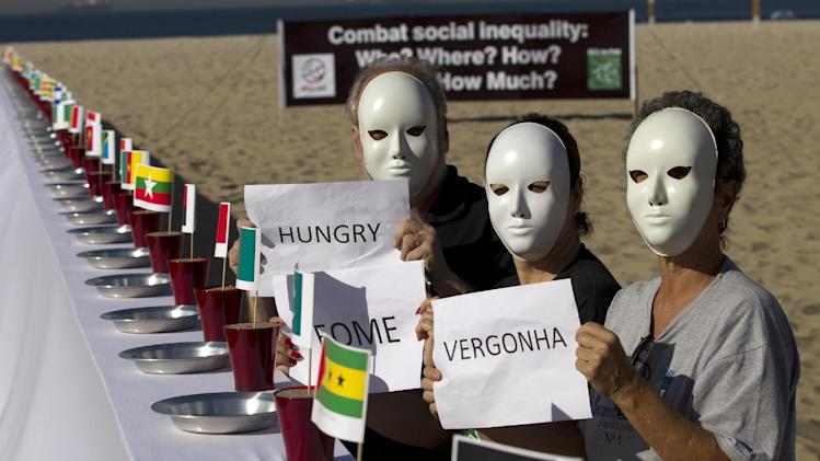 "People protest beside a table set with empty plates and national flags as they hold signs that read from right to left in Portuguese; ""Shame, hunger"" at the Copacabana beach during the United Nations Conference on Sustainable Development, or  Rio+20, in Rio de Janeiro, Brazil, Tuesday, June 19, 2012. The Earth summit runs through June 22. (AP Photo/Silvia Izquierdo)"
