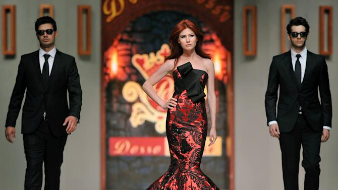 In this photo taken Friday, June 8, 2012, Russian ex-spy Anna Chapman, center, walks a Turkish catwalk flanked by two men posing as secret service agents at a fashion show in Antalya, Turkey. The 30-year-old Chapman was deported from the United States in 2010 along with nine other Russian sleeper agents. (AP Photo)