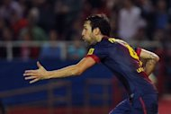 Barcelona's Cesc Fabregas celebrates after scoring during their Spanish La Liga match against Sevilla at the Ramon Sanchez Pizjuan stadium in Sevilla. Barcelona won 3-2