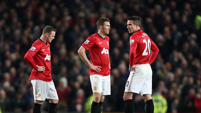 Manchester United's Wayne Rooney, left, Michael Carrick and Robin van Persie, right, react after Manchester City's Sergio Aguero scored during their English Premier League soccer match at Old Trafford Stadium, Manchester, England, Monday April 8, 2013. (AP Photo/Jon Super)