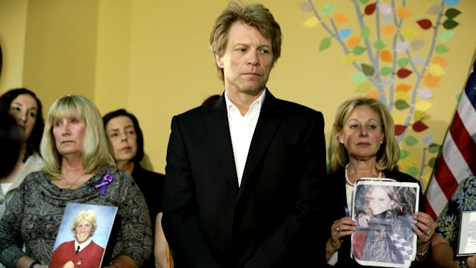 Singer Jon Bon Jovi, center, stands next to Pamela Sanquini, left, whose son Matthew overdose at the age of 20, and Jill LaZare, right, whose daughter Brooke overdose at age 23, as they listen to New Jersey Gov. Chris Christie talks about the signing of a good Samaritan bill intended to assure that a fear of prosecution doesn't get in the way of medical help for overdose victims, Thursday, May 2, 2013, in Paterson, N.J. The New Jersey law will shield from prosecution both overdose victims and those seeking medical help for them if they act in good faith. Bon Jovi's daughter suffered an apparent drug overdose on heroin in a dorm at Hamilton College in upstate New York last year. (AP Photo/Julio Cortez)