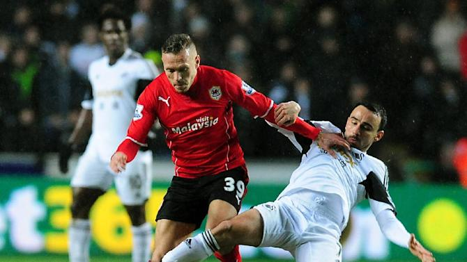 Swansea's Leon Britton, right, competes for the ball with Cardiff's Craig Bellamy during the English Premier League soccer match between Swansea City and Cardiff City at the Liberty Stadium, Swansea, Wales, Saturday, Feb. 8, 2014