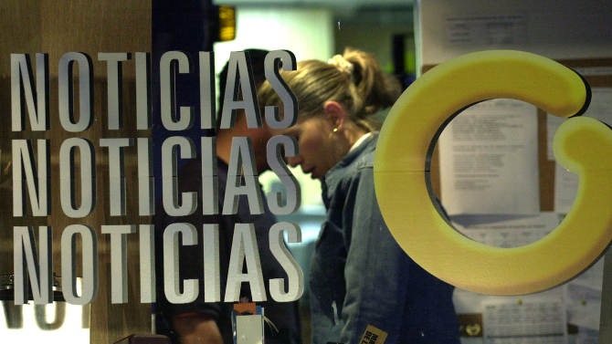 """FILE - In this Oct. 3, 2003 file photo, an employee at Globovision, a 24-hour television news channel, works behind a glass reading """"News"""" with Globovision's logo """"G"""" at the channel's headquarters in Caracas, Venezuela. Employees of the last remaining opposition television channel in Venezuela said on March 11, 2013 that it is being sold to a businessman friendly to the government. The employees said the sale would occur after April 14 elections, which Hugo Chavez's hand-picked successor is favored to win. (AP Photo/Leslie Mazoch, File)"""