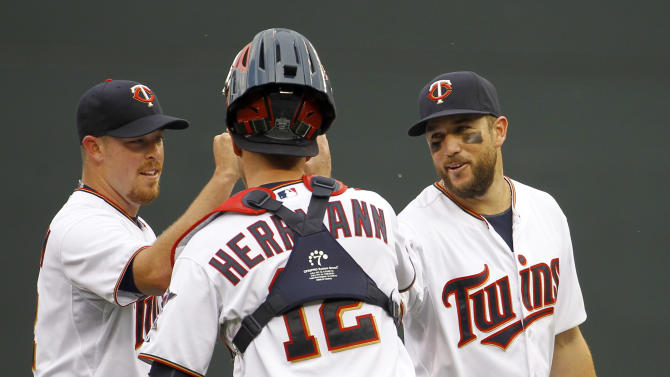 Minnesota Twins third baseman Trevor Plouffe, right, and pitcher J.R. Graham, left, celebrate with catcher Chris Herrmann (12) after the Twins defeated the Chicago White Sox 13-3 in a baseball game in Minneapolis, Sunday, May 3, 2015. (AP Photo/Ann Heisenfelt)