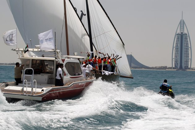 "Crew members wave from a dhow named ""Ghazi"", owned by Sheikh Sultan, during the Al Gaffal Traditional Dhow Sailing Race in Dubai"