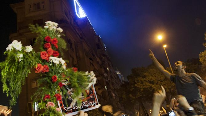 """An Egyptian man chants anti-Muslim Brotherhood slogans next to a cross made of flowers during a march marking the first anniversary of the victims who were killed during clashes with the military police in front of the National State T.V. building, known as Maspero, in Cairo, Egypt, Tuesday, Oct. 9, 2012. Muslim clerics, Christian priests, activists and former liberal lawmakers were among those marching to mark the anniversary of the """"Maspero massacre,"""" referring to the name of the state TV building, where the clashes broke out. (AP Photo/Khalil Hamra)"""