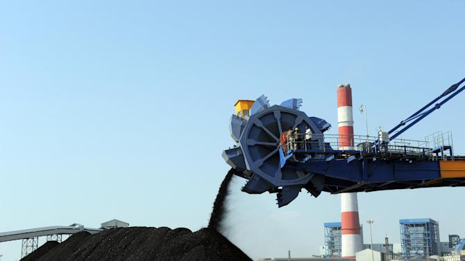 File photo taken in February 2011 shows workers using heavy machinery to sift through coal at the Adani Group's thermal power plant in Mundra, India
