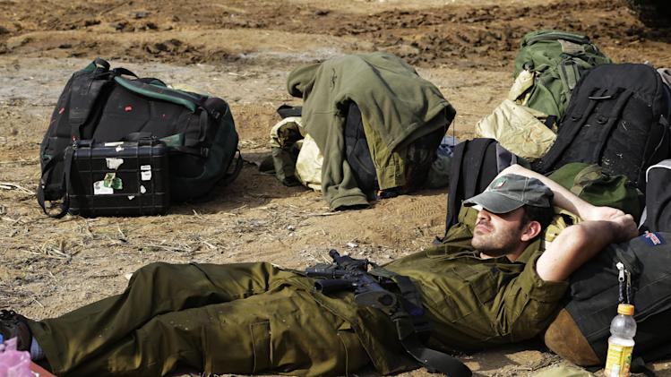 An Israeli soldier rests as he waits to be driven out of southern Israel, near the Israel Gaza Strip Border, Thursday, Nov. 22, 2012. A cease-fire agreement between Israel and the Gaza Strip's Hamas rulers took effect Wednesday night, bringing an end to eight days of the fiercest fighting in years and possibly signaling a new era of relations between the bitter enemies. (AP Photo/Lefteris Pitarakis)