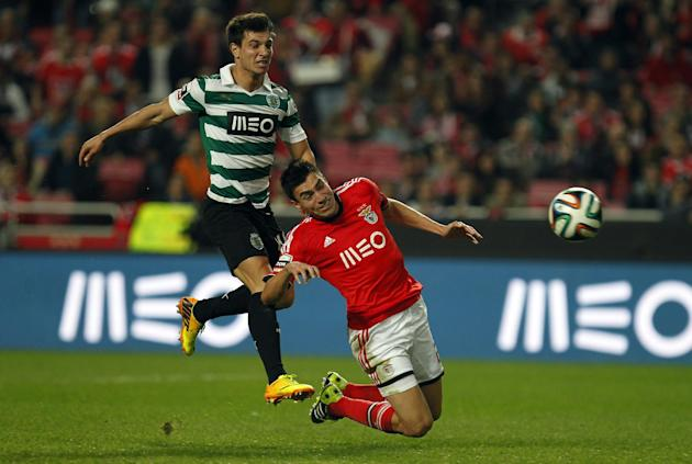 Benfica's Nico Gaitan, right, from Argentina, heads the ball to score the opening goal past Sporting's Cedric Soares during the Portuguese league soccer match between Benfica and Sporting at B