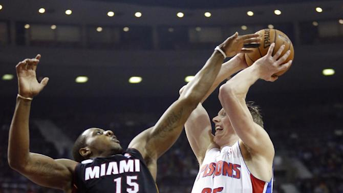Detroit Pistons forward Kyle Singler (25) goes to the basket against Miami Heat guard Mario Chalmers (15) in the first half of an NBA basketball game Friday, Dec. 28, 2012, in Auburn Hills, Mich. (AP Photo/Duane Burleson)