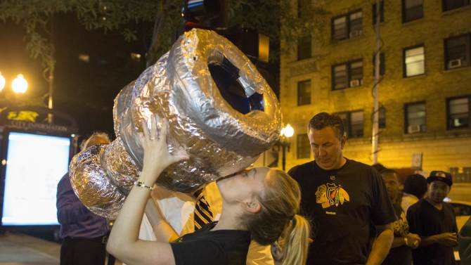 Fans celebrate on West Division Street with a homemade version of the Stanley Cup Trophy in Chicago after the Chicago Blackhawks won the NHL hockey Stanley Cup Finals on Monday, June 24, 2013. The Blackhawks defeated the Boston Bruins 3-2 in Game 6 to win the finals in Boston. (AP Photo/Scott Eisen)