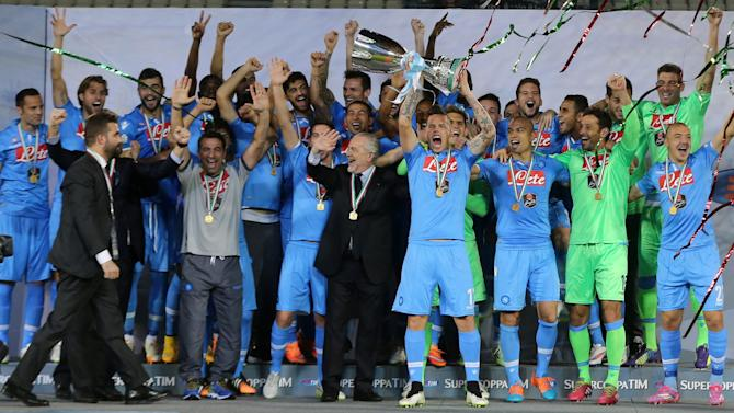 Napoli players celebrate with the trophy after winning their Italian Super Cup match against Juventus at Al-Sadd Stadium, in Doha,