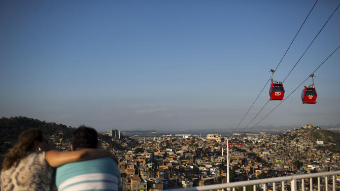 In this May 10, 2013 photo, a couple looks out over the the Complexo do Alemao slum where cable-cars move commuters above the homes in Rio de Janeiro, Brazil. The cable-car system linking six of Alemao's hilltops over a 3.5-kilometer (2.3-mile) route has become a popular tourist attraction. (AP Photo/Felipe Dana)