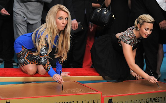 "Judges Britney Spears, left, and Demi Lovato sign their names during a handprint ceremony at ""The X Factor"" season two premiere at Grauman's Chinese Theatre on Tuesday, Sept. 11, 2012, in Los Angeles. (Photo by Jordan Strauss/Invision/AP)"