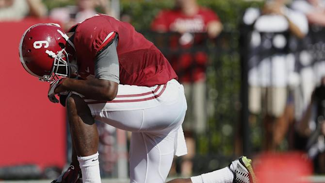 Alabama wide receiver Amari Cooper (9) kneels down in the end zone after scoring a touchdown against Florida in the first half of an NCAA college football game on Saturday, Sept. 20, 2014, in Tuscaloosa, Ala