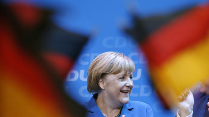 German chancellor Angela Merkel smiles behind German flags at the party headquarters in Berlin, Sunday, Sept. 22, 2013, after the first exit polls have been published. (AP Photo/Michael Sohn)