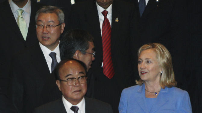 South Korean Foreign Minister Kim Sung-hwan, top left, walks by his North Korean counterpart Pak Ui Chun, bottom center, as U.S. Secretary of State Hillary Rodham Clinton talks with Japanese Foreign Minister Takeaki Matsumoto, center, prior to the start of ARF Retreat Session in Nusa Dua, Bali, Indonesia, Saturday, July 23, 2011. Clinton is telling North Korea that it must do more to improve ties with the South before the U.S. and other countries will return to nuclear disarmament talks. (AP Photo/Dita Alangkara)