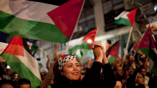 Palestinians cheer moments before their President Mahmoud Abbas addressed the General Assembly of the United Nations, in the West Bank city of Ramallah, Friday, Sept. 23, 2011. (AP Photo/Bernat Armangue)