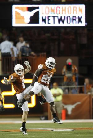 In this Sept. 10, 2011, photo, Texas' Quandre Diggs (28) celebrates with Jaxon Shipley during an NCAA college football game against BYU in Austin, Texas. Texas and Oklahoma cleared the way Monday, Sept. 19, 2011, for their departure from the Big 12 Conference, with regents at both powerhouse schools giving their presidents the authority to choose a new home. (AP Photo/Eric Gay)