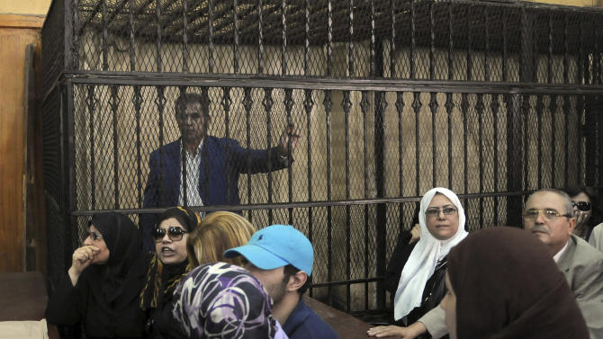 FILE - In this Saturday, Sept. 1, 2012 file photo, Tawfiq Okasha, a popular Egyptian TV presenter accused of inciting the killing of the country's new president on air, stands in the defendants cage at the opening of his trial, in Cairo, Egypt. Police say the trial of Okasha for inciting the murder of Egypt's Islamist president has been detained in connection with a series of allegations, including theft of electrical power and issuing a bounced check. (AP Photo/Mohammed Assad, File)