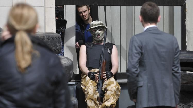 A pro-Russian armed man guards the city council building in the regional capital Donetsk