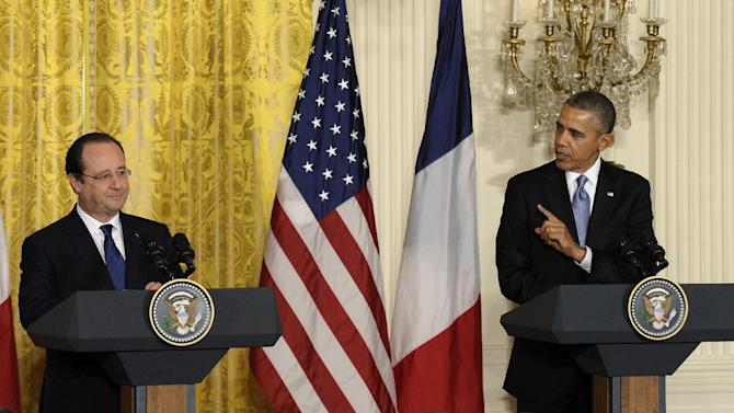 """President Barack Obama gestures toward French President François Hollande during their joint news conference, as part of an official state visit, Tuesday, Feb. 11, 2014, in the East Room of the White House in Washington. Lauding the """"enduring alliance"""" between the United States and France, President Barack Obama on Tuesday welcomed President Francois Hollande to the White House for a lavish state visit. The highly anticipated trip is taking place amid swirling speculation on both sides of the Atlantic about problems in Hollande's personal life. (AP Photo/ Susan Walsh)"""