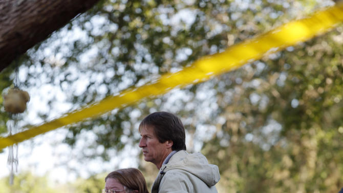 Family members watch as the home of Jeff Bush is destroyed Monday, March 4, 2013  in Seffner, Fla.  A sinkhole opened up underneath the house late Thursday, Feb. 28, 2013, swallowing Bush, 37.  The 20-foot-wide opening of the sinkhole was almost covered by the house, and rescuers said there were no signs of life since the hole opened Thursday night.  (AP Photo/Scott Iskowitz)