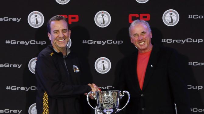 Hamilton Tiger Cats' Austin shakes hands with Calgary Stampeder's Hufnagel before the start of the coach's news conference at the CFL's 102nd Grey Cup week in Vancouver.