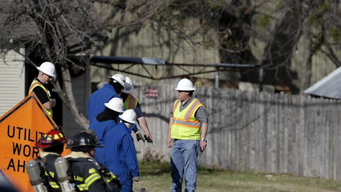 Lewisville fire fighters, bottom left, stage by an area with a water hose as workers look downward into a hole that was dug out nearly 100 feet away from a structure that exploded earlier Friday, Jan. 11, 2013, in Lewisville, Texas. An explosion Friday in a North Texas neighborhood leveled a home that is part of a local nonprofit's affordable housing program, injuring at least three men and scattering debris.(AP Photo/Tony Gutierrez)