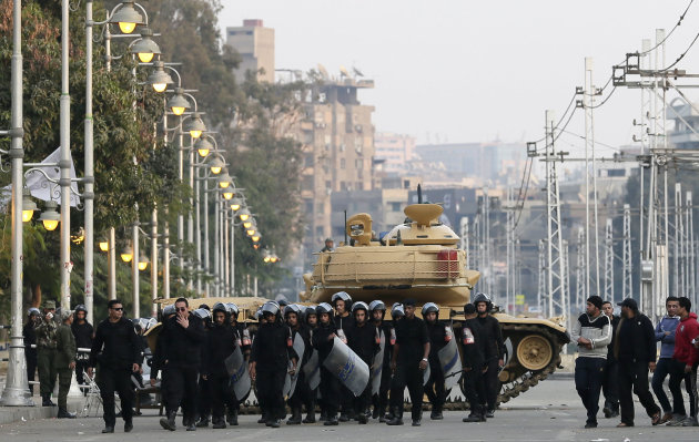 Egyptian riot police walk past a military tank guarding the presidential palace in Cairo, Egypt, Sunday, Dec. 16, 2012. Key Egyptian rights groups called Sunday for a repeat of the first round of the 