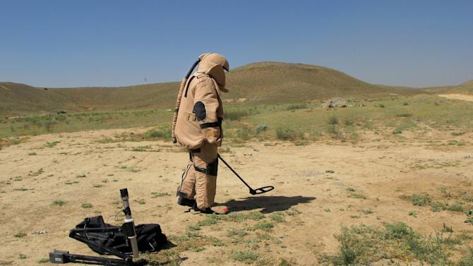 In this Tuesday, June 11, 2013 photo, Hayatuulah searches for land-mine with metal detector during an IED (improvised explosive device) defusing training exercise on the outskirts of Kabul, Afghanistan. A few years ago, there were almost no Afghan bomb disposal experts. Now, there are 369 _ and the international coalition is rushing to train hundreds more before the exit of most coalition forces by the end of next year. (AP Photo/Kay Johnson)