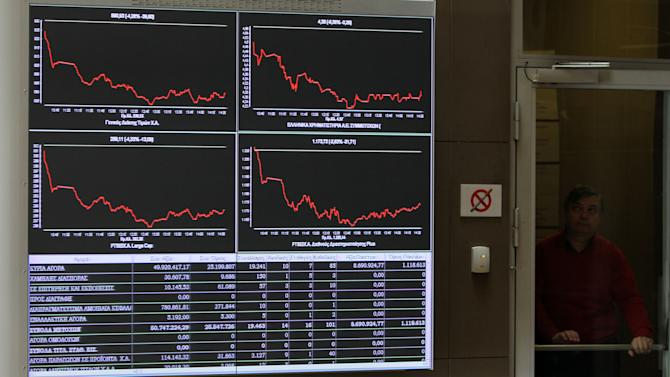 An employee of the Stock Exchange opens a door next to a display showing stock price movements  in Athens, Tuesday, March 26, 2013. Greece's Piraeus Bank reached an agreement Tuesday to buy the Greek operations of three Cypriot banks for euro524 million ($678 million). Despite the deal, the Athens Stock Exchange was down 5.5 percent on Tuesday as traders returned to their desk following a long weekend . Many European markets, particularly those at the forefront of Europe's debt crisis fell sharply Monday amid worries that big bank deposits may be raided in future financial bailouts. (AP Photo/Thanassis Stavrakis)