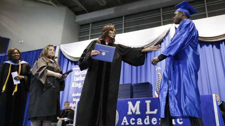First lady Michelle Obama, second from right, hands out diplomas at the graduation ceremony for Martin Luther King, Jr. Academic Magnet High School on Saturday, May 18, 2013, in Nashville, Tenn. (AP Photo/Mark Humphrey)