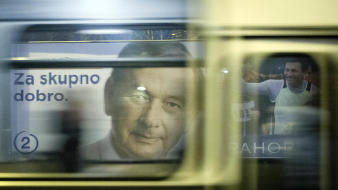Electoral posters of candidates Danilo Turk, left and Borut Pahor, right, are seen through a moving bus, in Ljubljana, Slovenia, Friday, Nov. 9, 2012. Three candidates are vying for the presidency this weekend in crisis-stricken Euro zone member Slovenia where deep political divisions have threatened efforts at reforms needed to avoid possible bailout. (AP Photo/Darko Bandic)