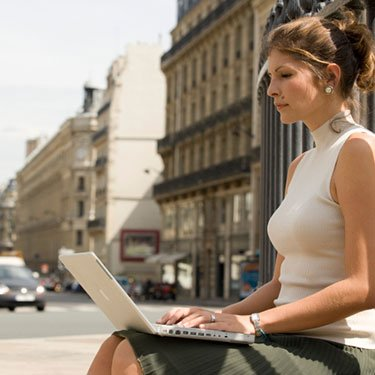 Woman-sitting-on-bench-in-street-using-laptop_web