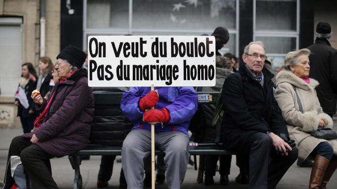"""A protestor holds a placard reading """"We want jobs, not gay marriage"""" during an anti gay marriage and gay adoption demonstration, in Paris, Sunday, March 24, 2013. Thousands of French conservatives, families and activists have converged on the capital to try to stop the country from allowing same-sex couples to marry and adopt children. The lower house of France's parliament approved the """"marriage for everyone"""" bill last month with a large majority, and it's facing a vote in the Senate next month. Both houses are dominated by French President Francois Hollande's Socialist Party and its allies. (AP Photo/Thibault Camus)"""