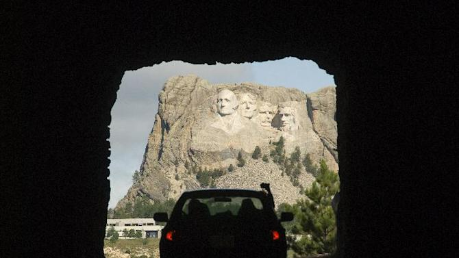 This undated photo provided by the South Dakota Department of Tourism shows a sneak peek of the famous presidents' faces of Mount Rushmore in the Black Hills of South Dakota. The view can be seen from Iron Mountain Road-Highway 16A. There is no entry fee to get into the park but parking for the view from inside will cost you $11. (AP Photo/www.travelsd.com)