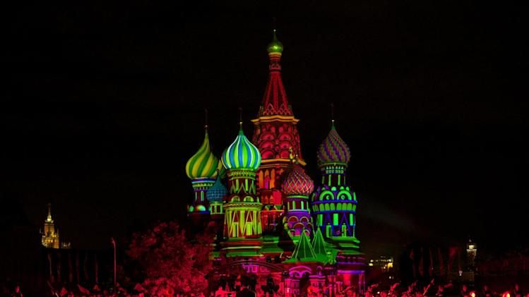 """St.Basil Cathedral is lit using show lights as Russian military cadets perform during the rehearsal of """"Spasskaya Tower"""" International Military Orchestra Music Festival at the Red Square in Moscow, Russia, Friday, Aug. 29, 2014. (AP Photo/Ivan Sekretarev)"""