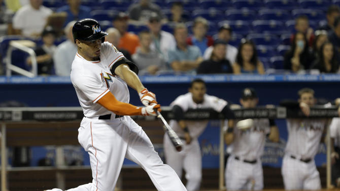 Miami Marlins' Giancarlo Stanton hits a double against the Atlanta Braves in the first inning of a baseball game, Wednesday, July 10, 2013, in Miami. Justin Ruggiano and Ed Lucas scored on the double. (AP Photo/Alan Diaz)