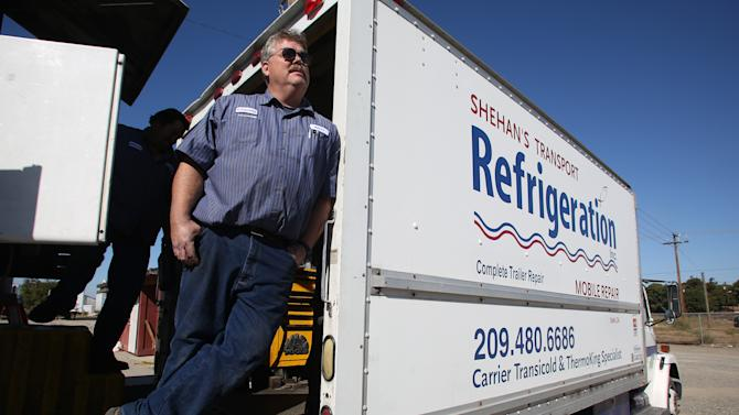 This photo taken Oct. 25, 2012 shows Kelly Cox, co-owner of Shehan's Transport Refrigeration stands in one of his trucks, in Delhi, Calif. Who are these people who still can't make up their minds? They're undecided voters like Cox, who spends his days repairing the big rigs that haul central California's walnuts, grapes, milk and much more across America. He doesn't put much faith in Barack Obama or Mitt Romney.  (AP Photo/Gary Kazanjian)