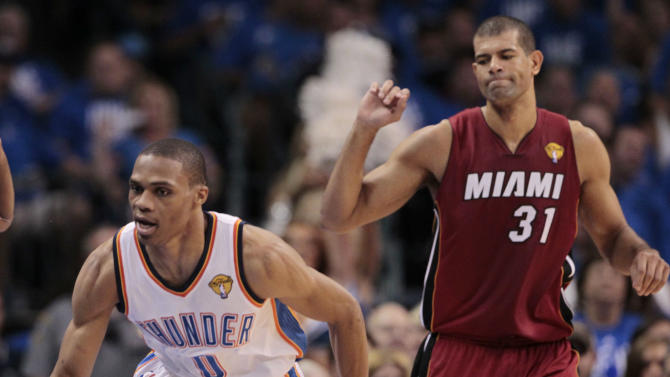 Oklahoma City Thunder point guard Russell Westbrook goes after a loose ball as Miami Heat small forward Shane Battier backs away during the first half at Game 1 of the NBA finals basketball series, Tuesday, June 12, 2012, in Oklahoma City. (AP Photo/Jeff Roberson)