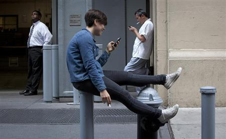 People smoke during a break outside an office building in midtown New York