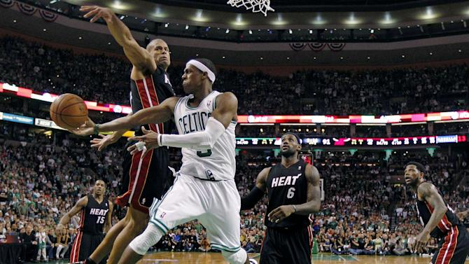 Boston Celtics' Rajon Rondo dumps off the ball as he is pressured by Miami Heat's Shane Battier, center left, during overtime of Game 4 in the NBA basketball Eastern Conference finals playoffs series, in Boston, Sunday, June 3, 2012. The Celtics won 93-91, tying the series at 2-2. (AP Photo/Charles Krupa)