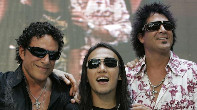 "FILE - In this March 2, 2009 file photo, Filipino singer-songwriter Arnel Pineda, center, the lead vocalist of American rock band ""Journey"" smiles beside bandmates Neal Schon, left, and Deen Castronovo, right, during a press conference at a mall in suburban Quezon City, north of Manila, Philippines. American rock band Journey's lead vocalist Pineda said he's been putting together an album of his own compositions in his own voice which he plans to release in 2014. The singer spoke in an interview Tuesday, April 8, 2014, during the launch of his version of the song ""Charity"" in the animated children's music video Cha-Ching on Cartoon Network. (AP Photo/Aaron Favila, File)"