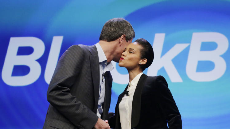 Thorsten Heins, CEO of Research in Motion, kisses Alicia Keys as he introduces her as the Global Creative director of Blackberry, Wednesday, Jan. 30, 2013 in New York. The maker of the BlackBerry smartphone is promising a speedy browser, a superb typing experience and the ability to keep work and personal identities separate on the same phone, the fruit of a crucial, long-overdue makeover for the Canadian company. (AP Photo/Mark Lennihan)