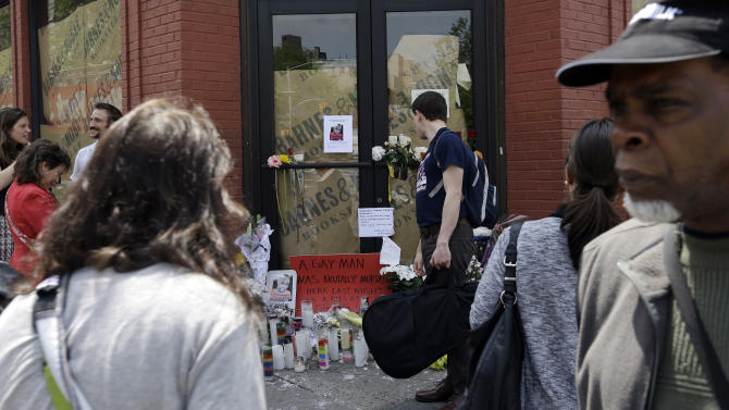 Pedestrians pass a makeshift memorial for 32-year-old Mark Carson, Monday, May 20, 2013, in New York. Police said Elliot Morales yelled anti-gay slurs before shooting Carson point-blank in the face in Greenwich Village, a neighborhood long known as a bedrock of the gay rights movement. (AP Photo/Frank Franklin II)