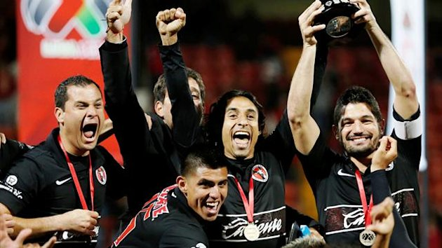 Tijuana captain Javier Gandolfi holds up the trophy as team-mates celebrate after winning the Mexican league championship final against Toluca (Reuters)