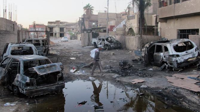 An Iraqi man inspects the aftermath of a bombing in the Baghdad al-Jadidah district, a mixed area under the control of Shiite militias in Baghdad, Iraq, Monday, Oct. 7, 2013. The attack is the latest in a relentless wave of killing that has made for Iraq's deadliest outburst of violence since 2008. (AP Photo/Khalid Mohammed)