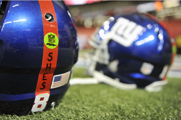 New York Giants helmets with a decal honoring the victims of the Sandy Hook Elementary School shooting rest on the turf before the first half of an NFL football game against the Atlanta Falcons, Sunda