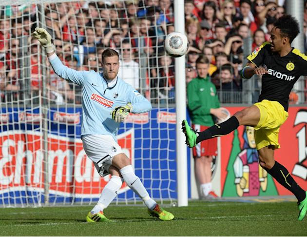 Dortmund's Pierre-Emerick Aubameyang, right, challenges for the ball with Freiburg's goalkeeper Oliver Baumann , left, during the GermanBundesliga soccer  match between SCFreiburg and Borussia